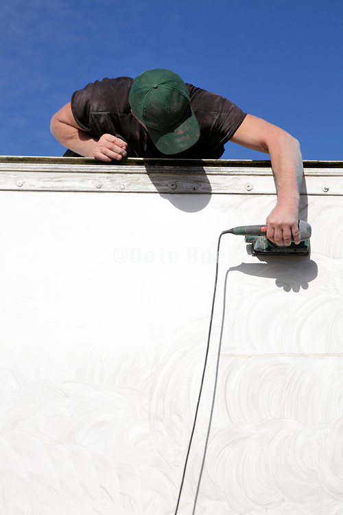 man sanding the side of a truck trailer