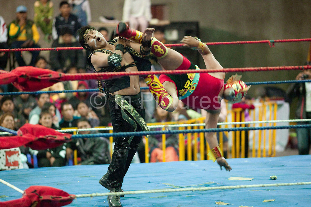 Male wrestler doing a flying kick move to opponent in ring. Lucha Libre wrestling origniated in Mexico, but is popular in other latin Amercian countries, including in La Paz / El Alto, Bolivia. Male and female fighters participate in the theatrical staged fights to an adoring crowd of locals and foreigners alike.
