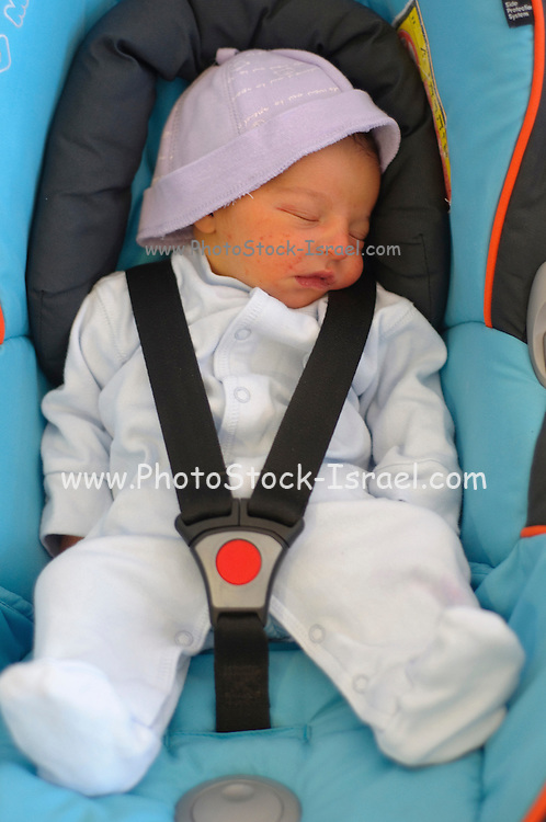 Baby boy sleeping strapped into a car seat