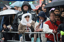 © London News Pictures. 01/01/2012. London, UK. Spectators watch the parade in heavy rain at the 2012 New Years Parade in London on January 1st, 2012. Photo credit : Ben Cawthra/LNP