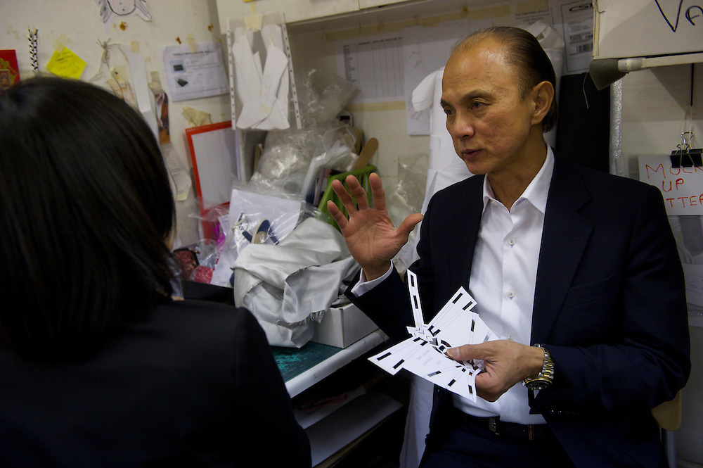 Fashion designer Jimmy Choo motions to staff in his studio on Cannaught Street, London, March 22, 2010