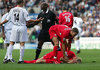 Photo. Andrew Unwin.<br /> Bolton Wanderers v Liverpool, Barclays Premiership, Reebok Stadium, Bolton 29/08/2004.<br /> Liverpool's Stephen Gerrard (R) checks on his team-mate, Sami Hyypia as he lies injured. Bolton's Kevin Davies (L)  pleads his innocence with the referee, Mr Uriah Renee (C)