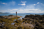 Antony Gormley sculpture GRIP of an abstract human form looking out over Saddell Bay, Kilbrannan Sound to Arran from rocks in Kintyre Peninsula, Scotland