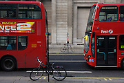 Two red buses and two bicycles locked to posts on opposite sides of the road outside the Bank of England in the City of London.