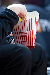 Middle aged man eating a bucket of popcorn during a basketball game
