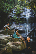 Two local guides sit on the rocks while tourists swim at Bigaho Falls near Port Barton, Palawan.
