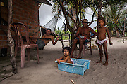 Eloi Ferreira, 58, rests on the hammock while he gets the visit of a cousin and watches his granddaughters playing on the backyard of his house. During the afternoons the children are free to walk around the oasis and the dunes and adults tend to visit each others houses and socialize.