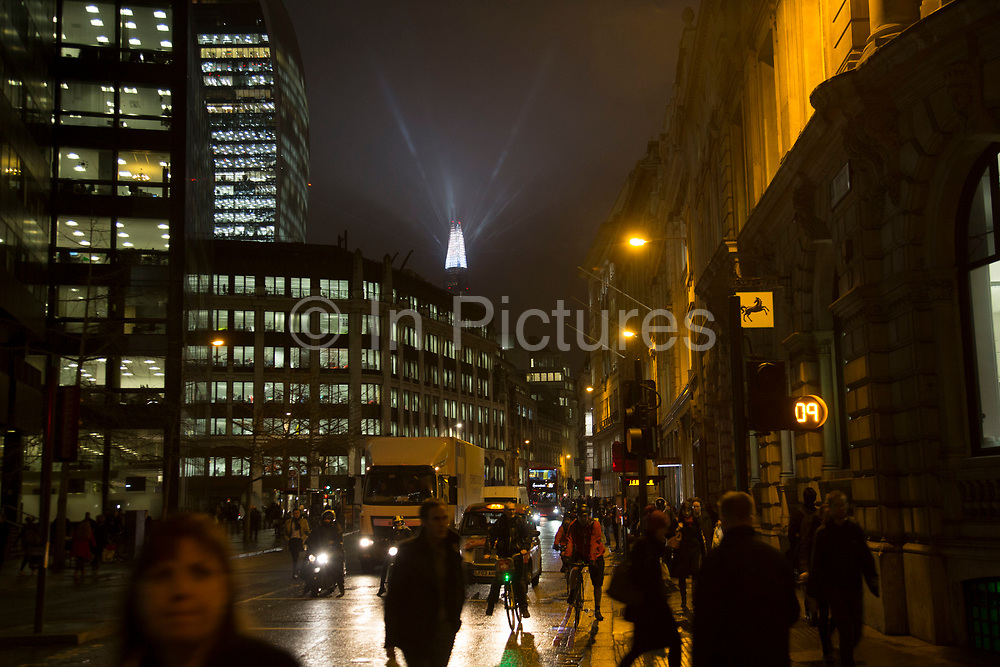 London's tallest skyscraper, the Shard, beams out spotlights in the distance in the City of London as part of a light show creating a public art installation in the sky on 13th December 2016 in London, England, United Kingdom.