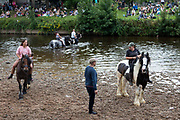 Crowds of onlookers sit on the banks of the River Eden, watching as various bareback riders wash their horses at Appleby Horse Fair, the biggest gathering of Gypsies and travellers in Europe, on 14th August, 2021 in Appleby, United Kingdom. Appleby Horse Fair attracts thousands from Gypsy, Romany, and traveller communities annually, making it the biggest gathering of its kind in Europe. Generally held for a week every June, the fair was postponed in 2020 and pushed forward to August in 2021 due to Coronavirus.
