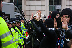 Whitehall, London, April 4th 2015. As PEGIDA UK holds a poorly attended rally on Whitehall, scores of police are called in to contain counter protesters from various London anti-fascist movements. PICTURED: Anti-fascist counter protesters raise their hands signifying they don't want violence between them and the police separating them from the PEGIDA rally.