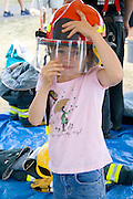 Girl age 6 wearing firefighters helmet at rescue demonstration and exhibit. Aquatennial Beach Bash Minneapolis Minnesota USA