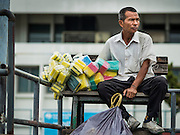 20 JULY 2015 - BANGKOK, THAILAND:   A sponge vendor waits to board a Chao Phraya Express Boat to take his sponges in to Bangkok. He is waiting a pier that is just south of the Chao Phraya River promenade project. The Chao Phraya promenade is development project of parks, walkways and recreational areas on the Chao Phraya River between Pin Klao and Phra Nang Klao Bridges. The 14 kilometer long promenade will cost approximately 14 billion Baht (407 million US Dollars). The project involves the forced eviction of more than 200 communities of people who live along the river, a dozen riverfront  temples, several schools, and privately-owned piers on both sides of the Chao Phraya River. Construction is scheduled on the project is scheduled to start in early 2016. There has been very little public input on the planned redevelopment.         PHOTO BY JACK KURTZ