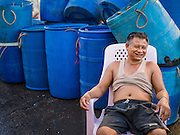 "11 JUNE 2015 - MAHACHAI, SAMUT SAKHON, THAILAND:  A Burmese migrant laborer relaxes during a break at the Talay Thai market in Mahachai. Labor activists say there are about 200,000 migrant workers from Myanmar (Burma) employed in the fishing and seafood industry in Mahachai, a fishing port about an hour southwest of Bangkok. Since 2014, Thailand has been a Tier 3 country on the US Department of State Trafficking in Persons Report (TIPS). Tier 3 is the worst ranking, being a Tier 3 country on the list can lead to sanctions. Tier 3 countries are ""Countries whose governments do not fully comply with the minimum standards and are not making significant efforts to do so."" After being placed on the Tier 3 list, the Thai government cracked down on human trafficking and has taken steps to improve its ranking on the list. The 2015 TIPS report should be released in about two weeks. Thailand is hoping that its efforts will get it removed from Tier 3 status and promoted to Tier 2 status.       PHOTO BY JACK KURTZ"