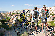 Bicycle riders looking at the Chimneys rock formation, Cappadocia, Turkey