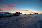A beautiful sunset turns certain layers of the sky in red and orange meanwhile members of the armed forces help a logistics transporter who slipped along the M12 highway driving towards Goris in Syunik province, southern Armenia on Sunday, Jan 24, 2021. No injuries reported. Heavy weather with blizzard led for black ice to form a layer in asphalt causing many heavy and light transporting vehicles to get stuck or slipping away from the main road. (Photo/ Vudi Xhymshiti)
