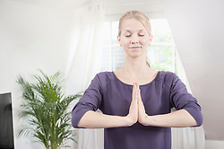 Young woman doing lotus pose yoga on in living room, Bavaria, Germany