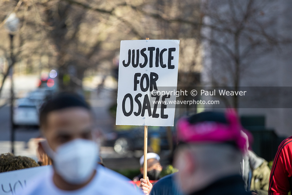 """A protester holds a sign reading """"justice for Osaze."""""""