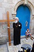 Israel, Jerusalem The Via Dolorosa Procession, Good Friday, Easter 2007. Priest stands next to a crucifix