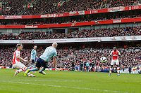 Arsenal's Aaron Ramsey scores his sides second goal despite the attentions of West Ham United's James Collins<br /> <br /> Photographer Craig Mercer/CameraSport<br /> <br /> Football - Barclays Premiership - Arsenal v West Ham United - Saturday 14th March 2015 - Emirates Stadium - London<br /> <br /> © CameraSport - 43 Linden Ave. Countesthorpe. Leicester. England. LE8 5PG - Tel: +44 (0) 116 277 4147 - admin@camerasport.com - www.camerasport.com