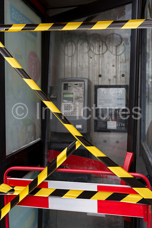 Hazard tape stretched across the glass of an old telephone kiosk on Tottenham Court Road, on 3rd August 2017, in London, England.