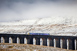 © Licensed to London News Pictures. 10/11/2016. Ingleton UK. A train passes over the Ribblehead viaduct in the shadow of the snow covered Whernside mountain in the Yorkshire Dales. Photo credit: Andrew McCaren/LNP