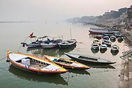 Boats in the mist at dawn on the River Ganges, Varanasi, Uttar Pradesh, India