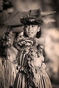 A young girl with outstretched arms dancing the hula in front of other hula dancers.Pictures of Hawaii.