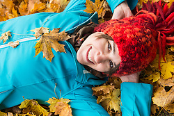 Close-up of smiling woman lying on ground in heap of autumn leaves