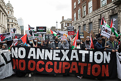 Activists march behind a banner during the National Demonstration for Palestine from Victoria Embankment to Hyde Park on 22nd May 2021 in London, United Kingdom. The demonstration was organised by pro-Palestinian solidarity groups in protest against Israel's recent attacks on Gaza, its incursions at the Al-Aqsa mosque and its attempts to forcibly displace Palestinian families from the Sheikh Jarrah neighbourhood of East Jerusalem.