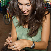 Peace Corps volunteer Rachael helps a young girl get ready for Islamic New Year by braiding her hair at the Sunday market near Koumbadiouma. Kolda, Senegal.