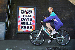 © Licensed to London News Pictures. 05/04/2020. London, UK. A woman on a bicycle rides past 'PLEASE BELIEVE THESE DAYS WILL PASS' sign in north London during a pandemic outbreak of the coronavirus. Photo credit: Dinendra Haria/LNP