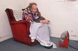 Elderly woman wrapped in blanket sitting in armchair in front of portable electric heater,