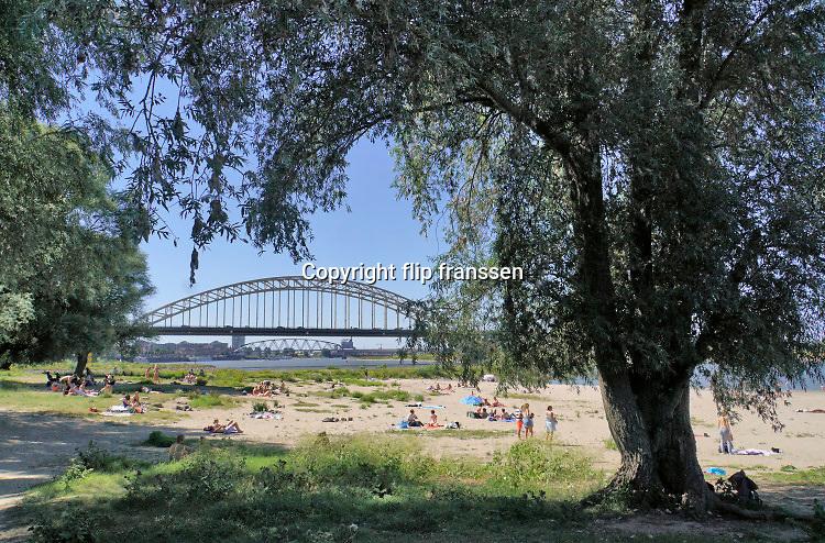 Nederland, nijmegen, 5-8-2020  Vooral jonge mensen zoeken verkoeling aan de oevers van de waal op deze tropisch warme nazomerdag . Het is eigenlijk verboden in de rivier te zwemmen vanwege de stroming en het drukke scheepvaartverkeer . Deze strandje liggen tussen de kribben in de Stadswaard . Foto: ANP/ Hollandse Hoogte/ Flip Franssen