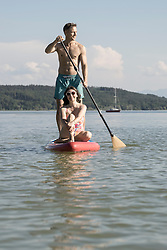 Mature couple paddleboarding in the lake, Bavaria, Germany