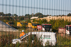 West Hyde, UK. 9th September, 2020. Trucks queue as anti-HS2 activists use a tripod to block one of several entrances blocked to the Chiltern Tunnel South Portal site for the HS2 high-speed rail link. The protest action, at the site from which HS2 Ltd intends to drill a 10-mile tunnel through the Chilterns, was intended to remind Prime Minister Boris Johnson that he committed to remove deforestation from supply chains and to provide legal protection for 30% of UK land for biodiversity by 2030 at the first UN Summit on Biodiversity on 30th September.
