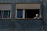BARCELONA, SPAIN - APRIL 26: An elderly woman looks on from her window on April 26, 2020 in Barcelona, Spain. Children in Spain, which has had one of the stricter lockdowns in Europe, are now allowed to leave their homes for up to an hour per day. The country has had more than 220,000 confirmed cases of COVID-19 and over 20,000 reported deaths, although the rate has declined after weeks of quarantine measures.