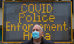 © Licensed to London News Pictures. 26/11/2020. Bexleyheath, UK. A man wearing a protective mask in front of a covid warning sign shopping in Bexleyheath Broadway, Greater London this morning who will go into tier two coronavirus restrictions but their Kent neighbours will get a tier three rating. The health secretary Matt Hancock has announced the new toughened up tier measures today that will come into effect next Wednesday when England's month long lockdown comes to an end. Photo credit:Grant Falvey/LNP