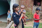 Tabasum Khatun, 14, is holding a toddler while standing near her home in Algunda village, pop. 1000, Giridih District, rural Jharkhand, India.