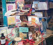 Religious, spiritual products on display in bookshop window, Glastonbury, Somerset, England