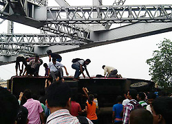 June 16, 2017 - Kolkata, India - Passenger Mini Bus Accident at Howrah Bridge ,2 killed after bus overturns on Howrah Bridge on June 16,2017 in Kolkata,India. The accident took place around 10.58 am when the Sealdah-bound minibus dashed against the road divider and lost control while overtaking another bus when it was descending from the bridge, a senior officer of Kolkata Traffic Police said.......Two children were among the injured and were rushed to a hospital. The police were yet to establish the identities of the victims...The accident led to a huge traffic jam on the bridge...The driver fled the scene after the incident. (Credit Image: © Debajyoti Chakraborty/NurPhoto via ZUMA Press)