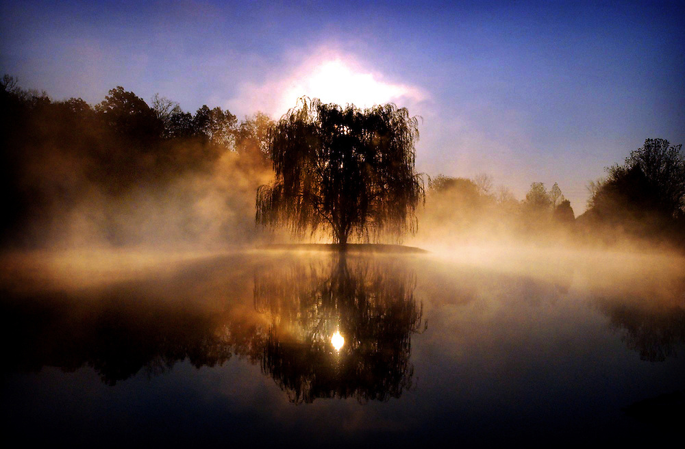 The sun rises over the outskirts of Bardstown, Ky., while a morning fog rises off a pond.