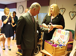 Prince Charles (known as The Duke of Rothesay when in Scotland) is given gifts during his visit to the Ayrshire Hospice in Ayr where he met patients and their families, staff and volunteers, with standing-volunteer occupational therapist George Bell (left) and patient Jim Fitzsimmons (centre right) and occupational therapist Joan Carrigan (right).