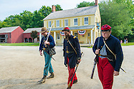 """Old Bethpage, New York, USA. August 30, 2015. At center, ANDREW PREBLE from Long Beach portrays an American Civil War Captain from the 14th Brooklyn Regiment (14th New York State Militia) AKA The Brooklyn Chasseurs, in front of the yellow and white Noon Inn tavern during the Old Time Music Weekend at the Old Bethpage Village Restoration. During their historical reenactments, members of the non-profit 14th Brooklyn Company E wear accurate reproductions of """"The """"Red Legged Devils"""" original Union army uniform."""