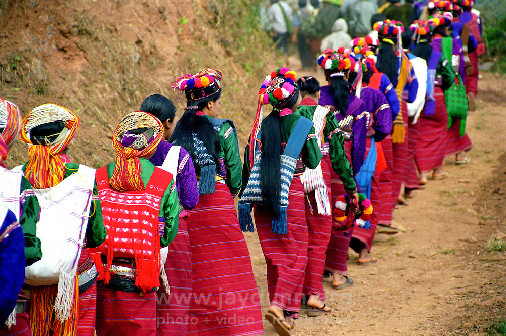 """BURMA / MYANMAR. Shan State, Kalaw, Peinnebin Village, 2003. Women in the lead, Wan Tha's wedding procession arrives in Peinnebin after a full day's journey, dressed in their finest """"longyis,"""" or traditional skirts."""