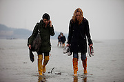 "Two women with long rubber boots are walking on the slowly closing ""Mysterious Sea Road"" in Hoedong shore (Jindo island). Jindo is the 3rd biggest island in South Korea located in the South-West end of the country and famous for the ""Mysterious Sea Route"" or ""Moses Miracle"". Every spring thousands flock to the shores of Jindo to walk the mysterious route that stretches roughly three kilometers from Hoedong to the distant island of Modo. Materializing from the rise and fall of the tides, the divide can reach as wide as forty meters."