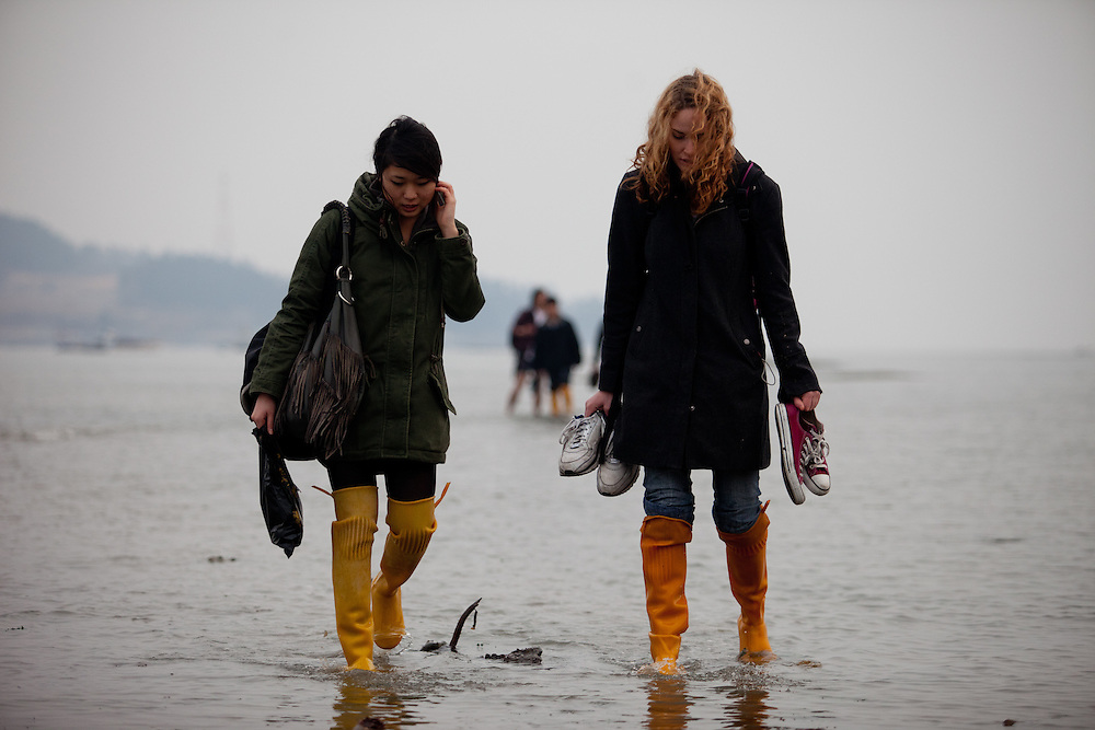 """Two women with long rubber boots are walking on the slowly closing """"Mysterious Sea Road"""" in Hoedong shore (Jindo island). Jindo is the 3rd biggest island in South Korea located in the South-West end of the country and famous for the """"Mysterious Sea Route"""" or """"Moses Miracle"""". Every spring thousands flock to the shores of Jindo to walk the mysterious route that stretches roughly three kilometers from Hoedong to the distant island of Modo. Materializing from the rise and fall of the tides, the divide can reach as wide as forty meters."""