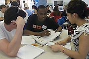 Somali immigrant Cabdisalan Mohammed, center, gets help with his homework from University of Louisville student volunteers Justin Snow, left, and Insha Hague during the English Conversation Club: Dance and Dialogue event Saturday April 9, 2011 at the Iroquois Branch of the Louisville Free Public Library in Louisville, Ky. Henna and Bindi followed the Bollywood dance lesson, and then volunteers were paired with English language learners to work on conversation skills. (Photo by Brian Bohannon)
