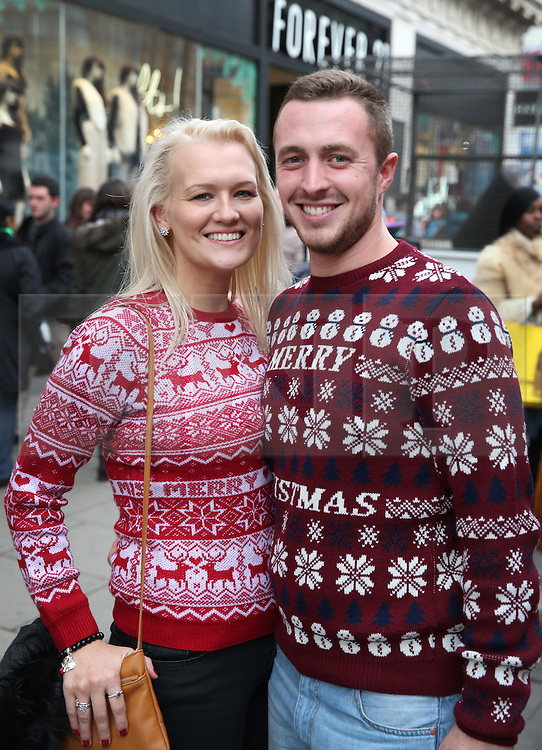 © Licensed to London News Pictures. 19/12/2015. London, UK. A couple wear Christmas jumpers as they look for bargains in Oxford Street on the last Saturday before Christmas. Photo credit: Peter Macdiarmid/LNP