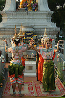 Fawn Thai classical dancers at the Phra Mae Thorani shrine who is a Thai  Goddess of the Earth.  She is often shown wringing  waters of detachment out of her hair. The water drowns the forces of temptation sent by demons to distract the Buddha as he meditated under the Bodhi tree.