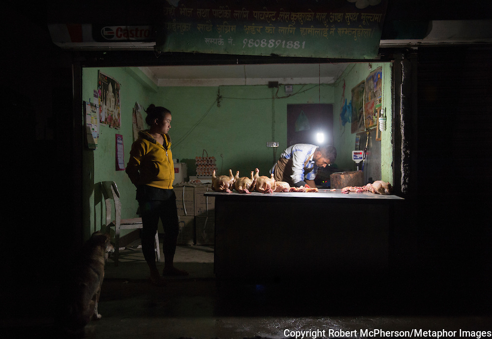 A rear view, this butcher in Kathmandu uses a simple lamp for working late hours in his shop. Nepal is the second richest country in water resource but they still meet challenges with building hydropower. Everyday electric current goes off for hours and people are compelled to live in the darkness. Norway is one of the countries who have earned a lot of money on building hydropower in Nepal, but the country itself still remains poor and undeveloped. After the earthquakes that struck Nepal in 2015 the situation is even worse.